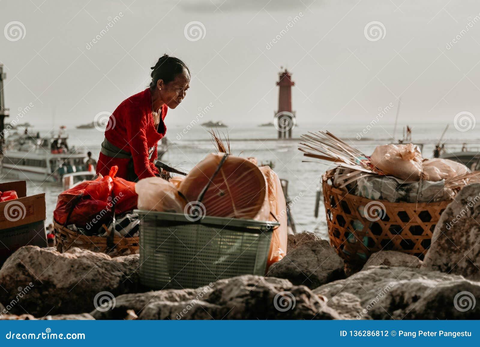 Ηλικιωμένη γυναίκα κατά να προετοιμάσει τα αγαθά πριν πέρα από το στενό Badung