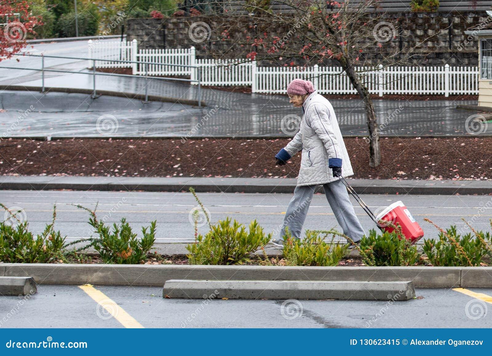 Ηλικιωμένη γυναίκα που περπατά στη βροχή