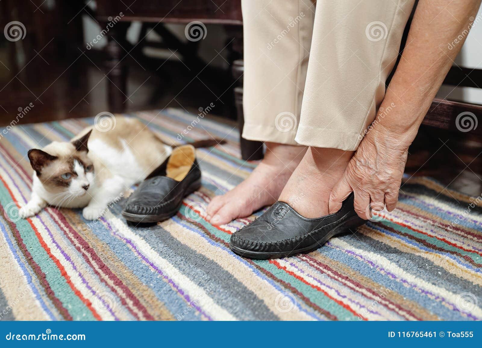 Ηλικιωμένη γυναίκα που πρήζεται πόδια που βάζουν στα παπούτσια