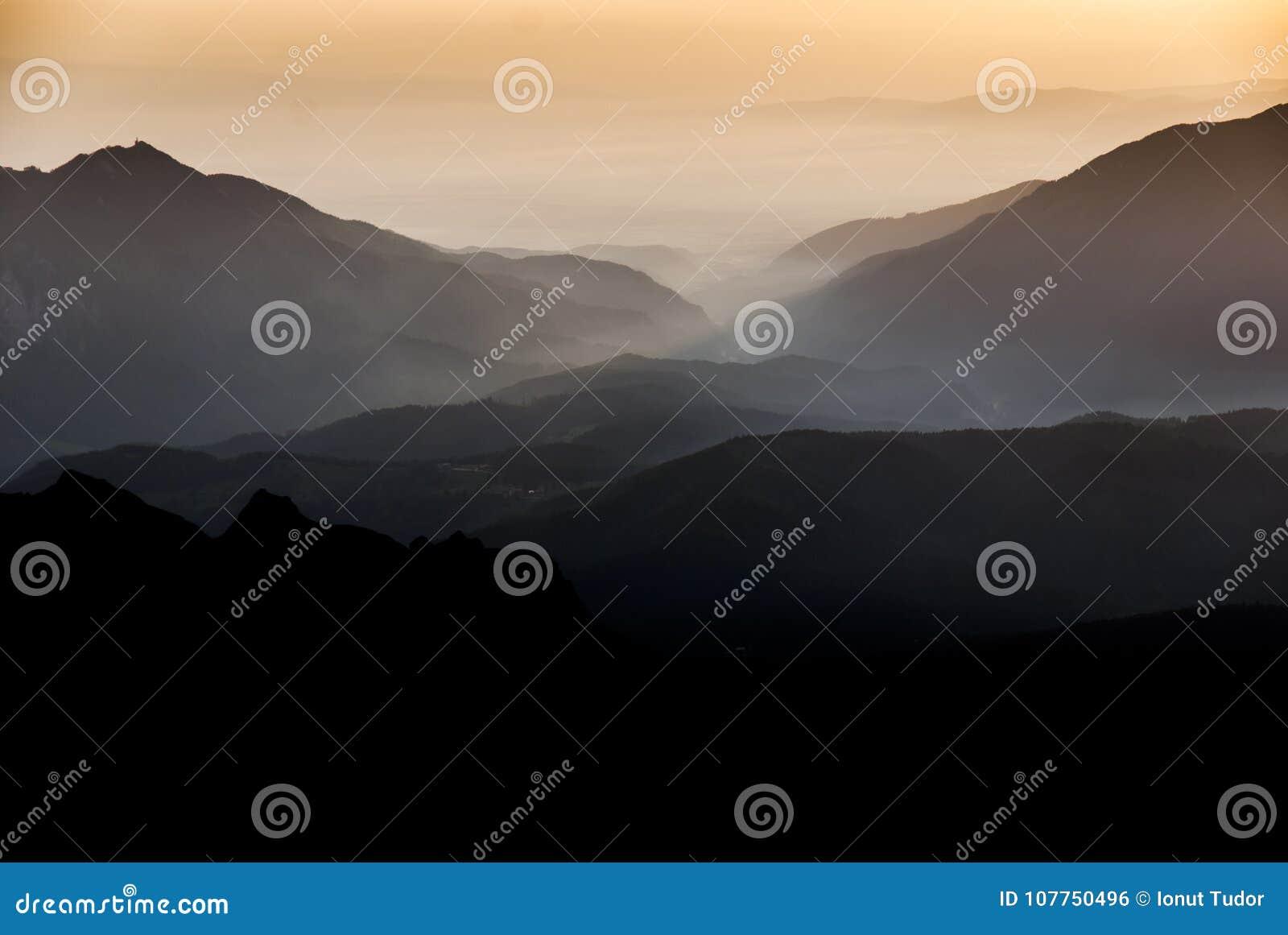 Ηλιοβασίλεμα επάνω από τις κορυφογραμμές και τις κοιλάδες βουνών