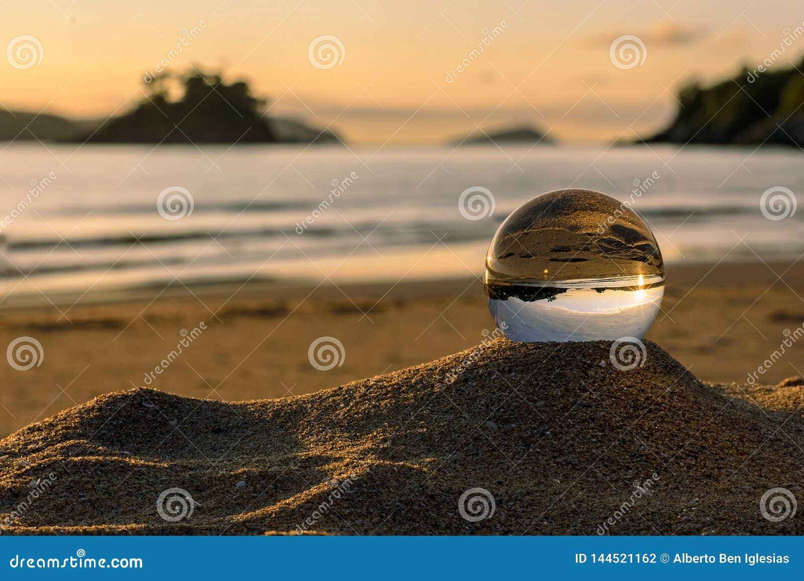 Ηλιοβασίλεμα και παραλία σε μια σφαίρα κρυστάλλου