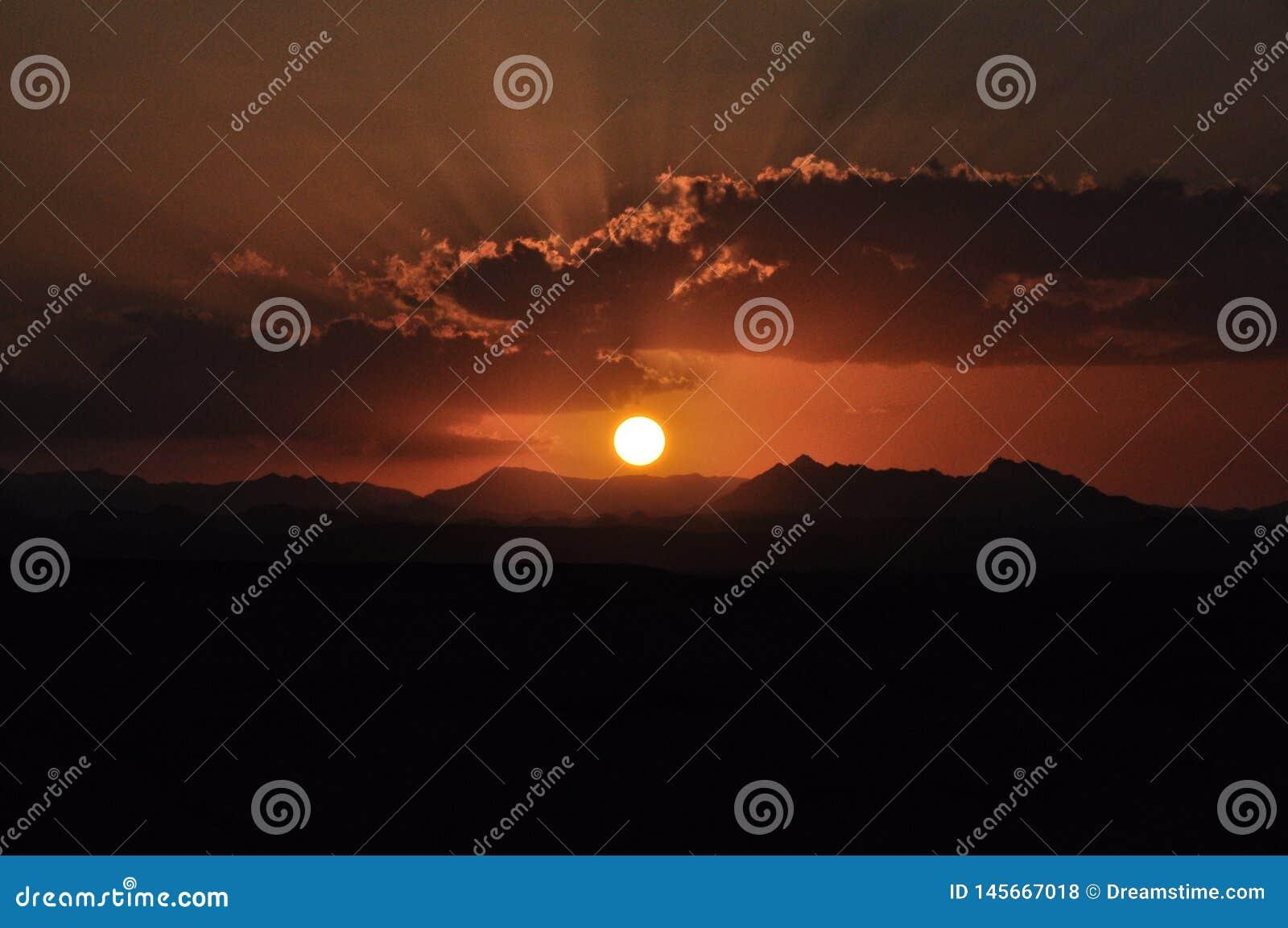Ηλιοβασίλεμα πέρα από τα βουνά με τον ήλιο που λάμπει μέσω των σύννεφων