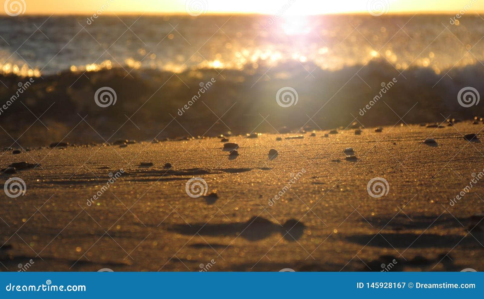 Ηλιοβασίλεμα στην Ελλάδα σε μια παραλία με την άμμο στο πρώτο πλάνο