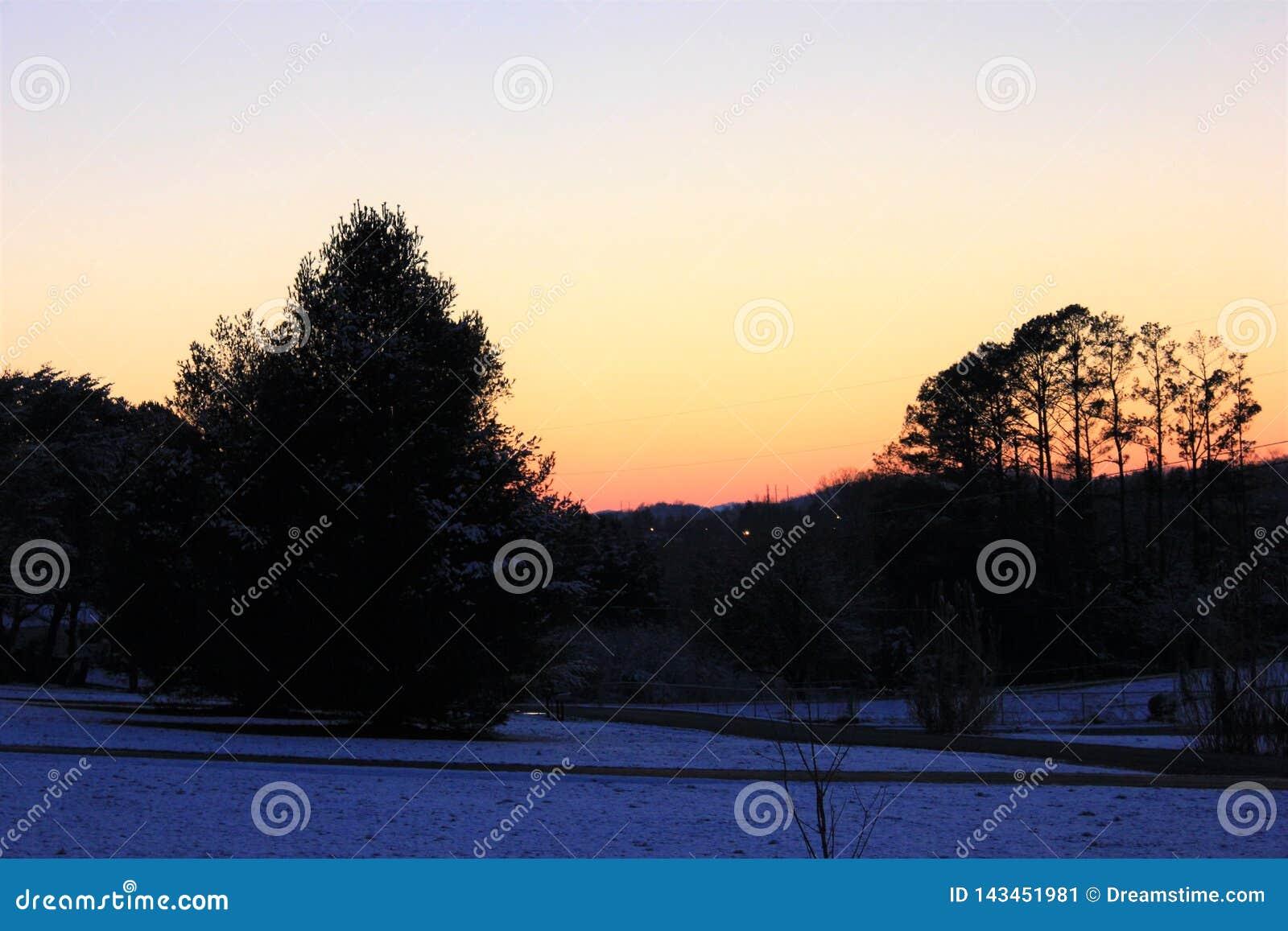 Ηλιοβασίλεμα το χειμώνα που πλαισιώνεται από τα όμορφα δέντρα