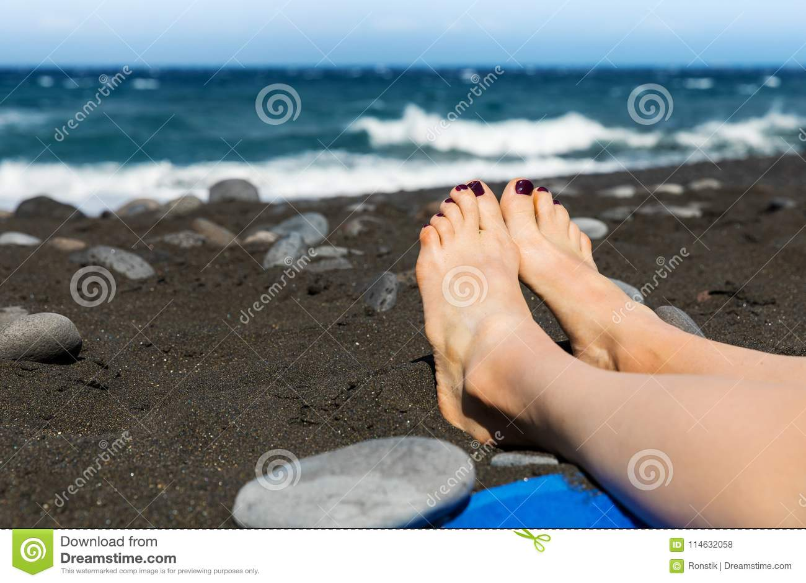 5320fd6ce5 Ηλιοθεραπεία - πόδια γυναικών στη μαύρη παραλία άμμου Στοκ Εικόνες ...