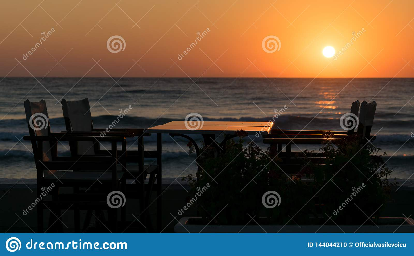 Ηλιοθεραπεία στην παραλία με να καθίσει και να δειπνήσει την επιτραπέζια σκιαγραφία για το πρόγευμα και τη θάλασσα με τα κύματα