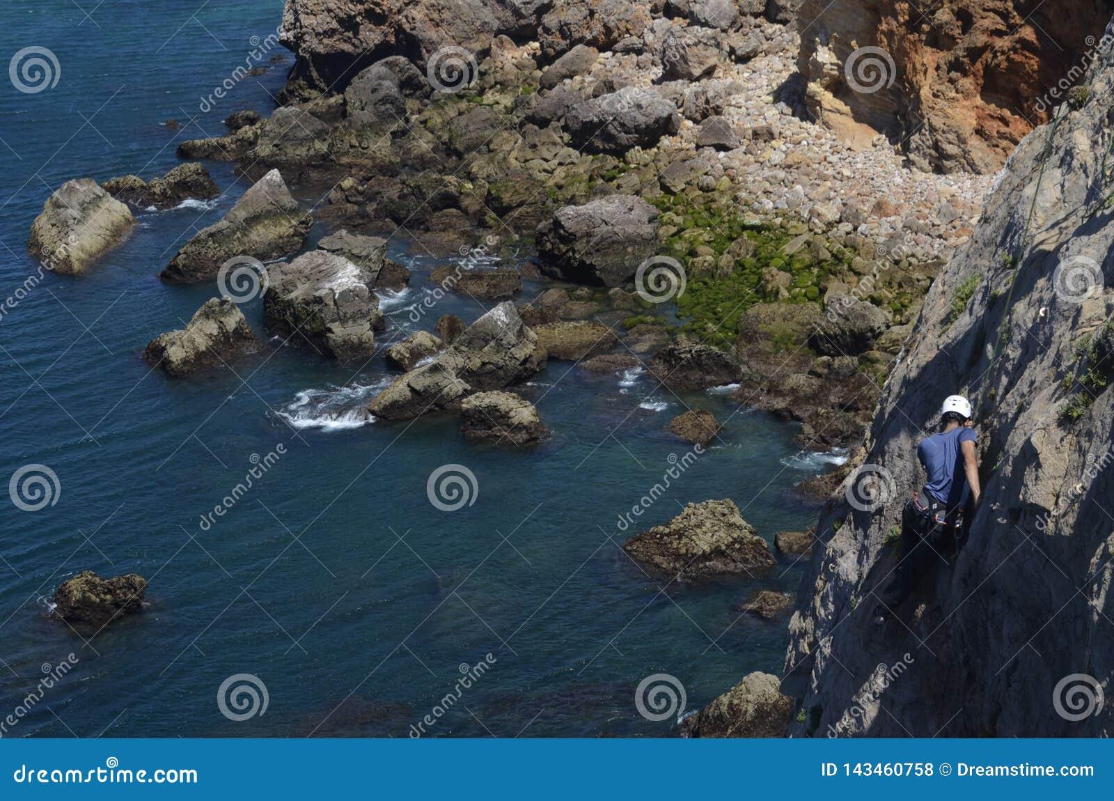 Ηλιόλουστη ημέρα της αναρρίχησης στους απότομους βράχους πετρών στην Πορτογαλία με τους ορειβάτες