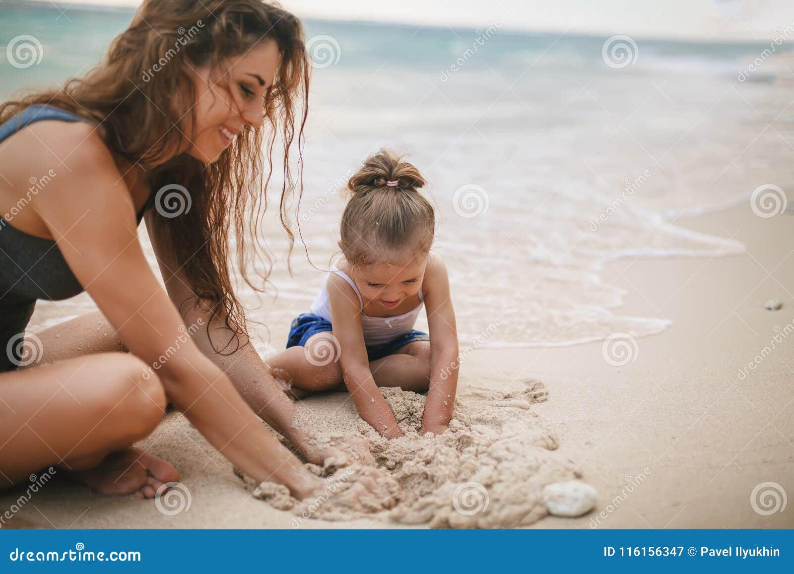 Ημέρα παιδιών ` s Παιχνίδι Mom και μωρών κοντά στην παραλία