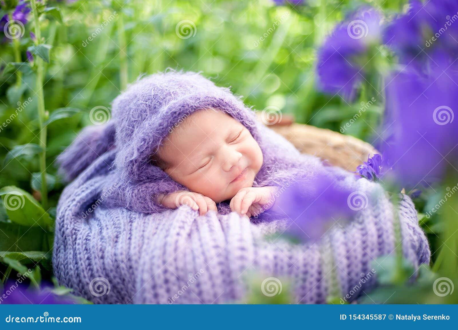 17 ημέρα που χαμογελά το νεογέννητο μωρό κοιμάται στο στομάχι του στο καλάθι στη φύση στον κήπο υπαίθριο