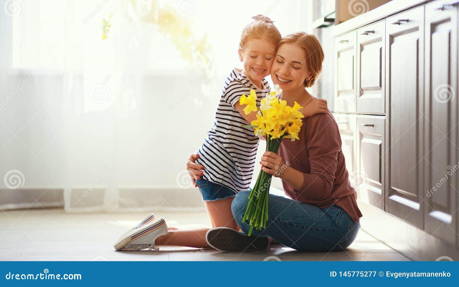 Ημέρα της ευτυχούς μητέρας! η κόρη παιδιών δίνει στη μητέρα μια ανθοδέσμη των λουλουδιών στους ναρκίσσους και το δώρο