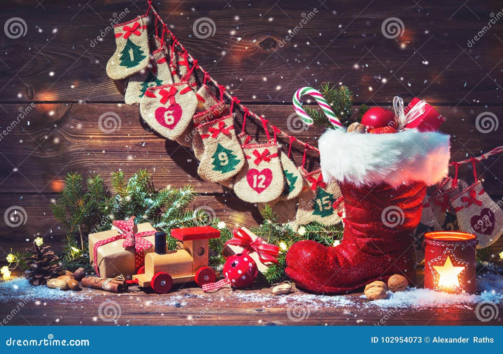 Ημερολόγιο εμφάνισης και παπούτσι Santa ` s με τα δώρα στην αγροτική ξύλινη ΤΣΕ