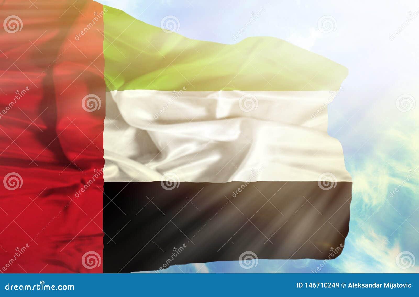 Ηνωμένα Αραβικά Εμιράτα που κυματίζουν τη σημαία ενάντια στο μπλε ουρανό με τα sunrays