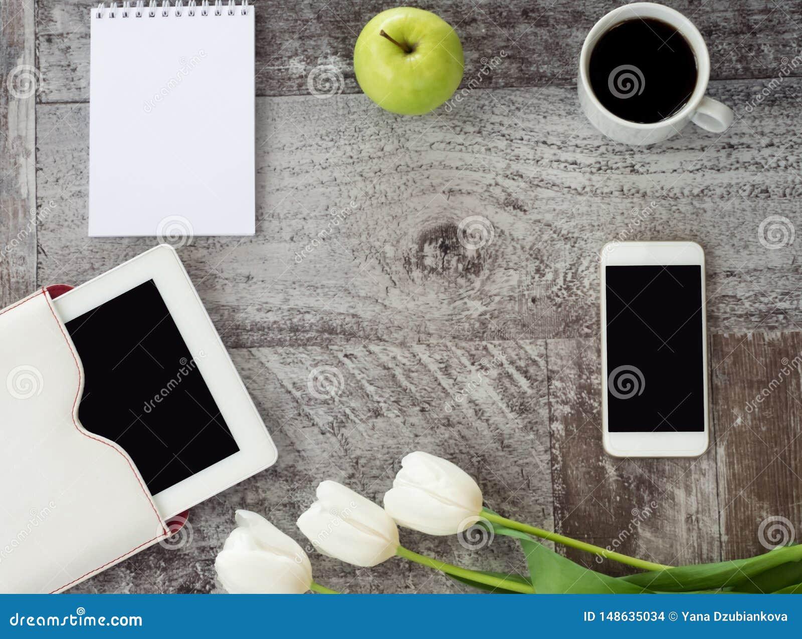 Η άσπρη ταμπλέτα, το τηλέφωνο, το φλιτζάνι του καφέ, το σημειωματάριο, το πράσινα μήλο και τα λουλούδια είναι στον πίνακα r