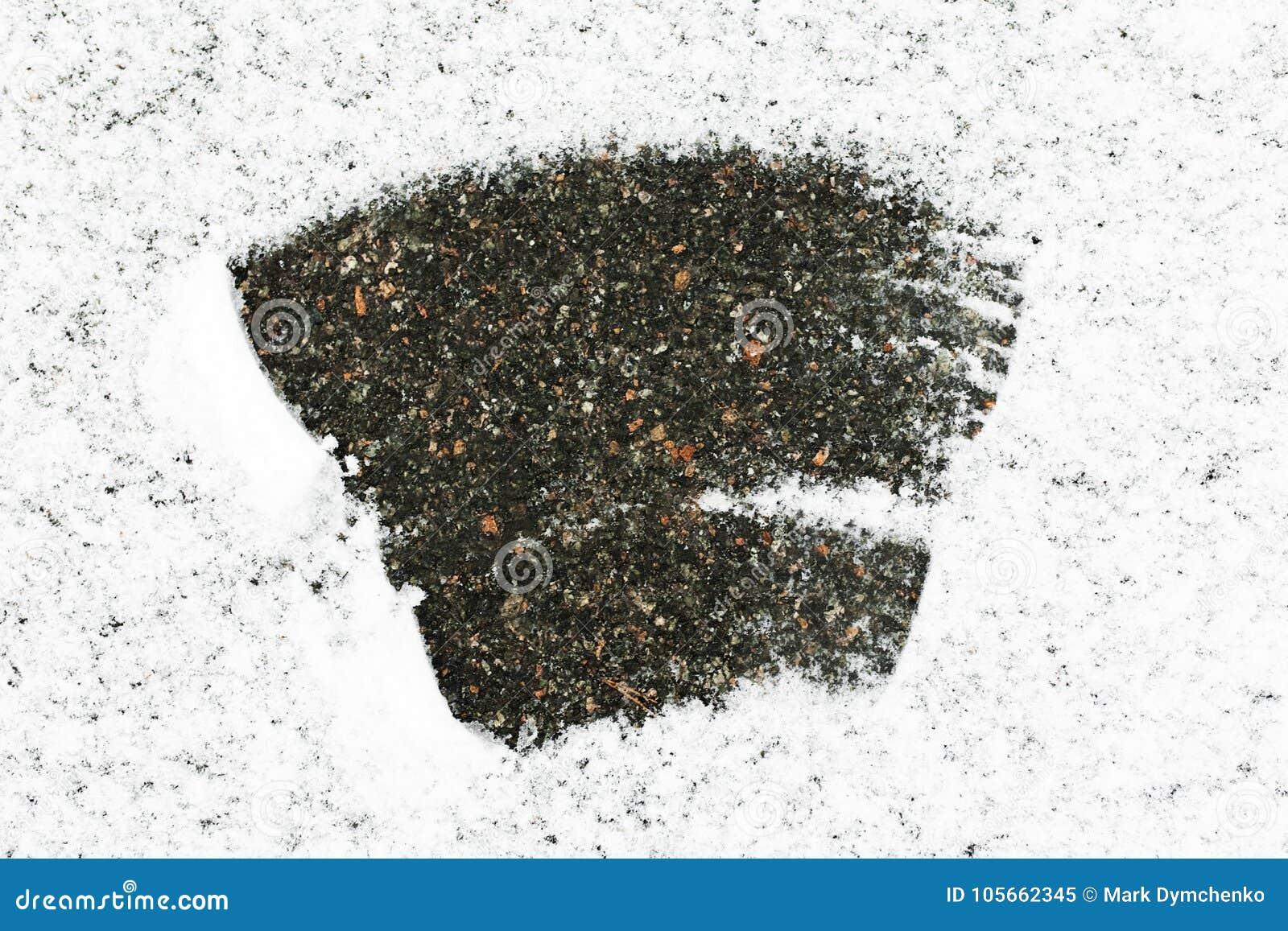 Η άσφαλτος που καλύπτεται με το χιόνι, μέρη του χιονιού στη μέση του χιονιού που καθαρίζεται, υπόβαθρο χιονιού
