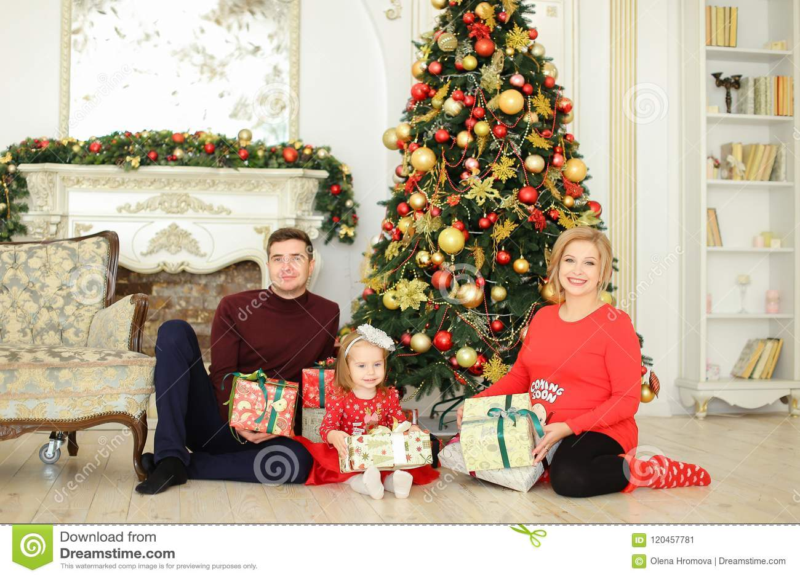 Η έγκυος ξανθή συνεδρίαση γυναικών με τον άνδρα και λίγη κόρη κοντά στο χριστουγεννιάτικο δέντρο και παρουσιάζει