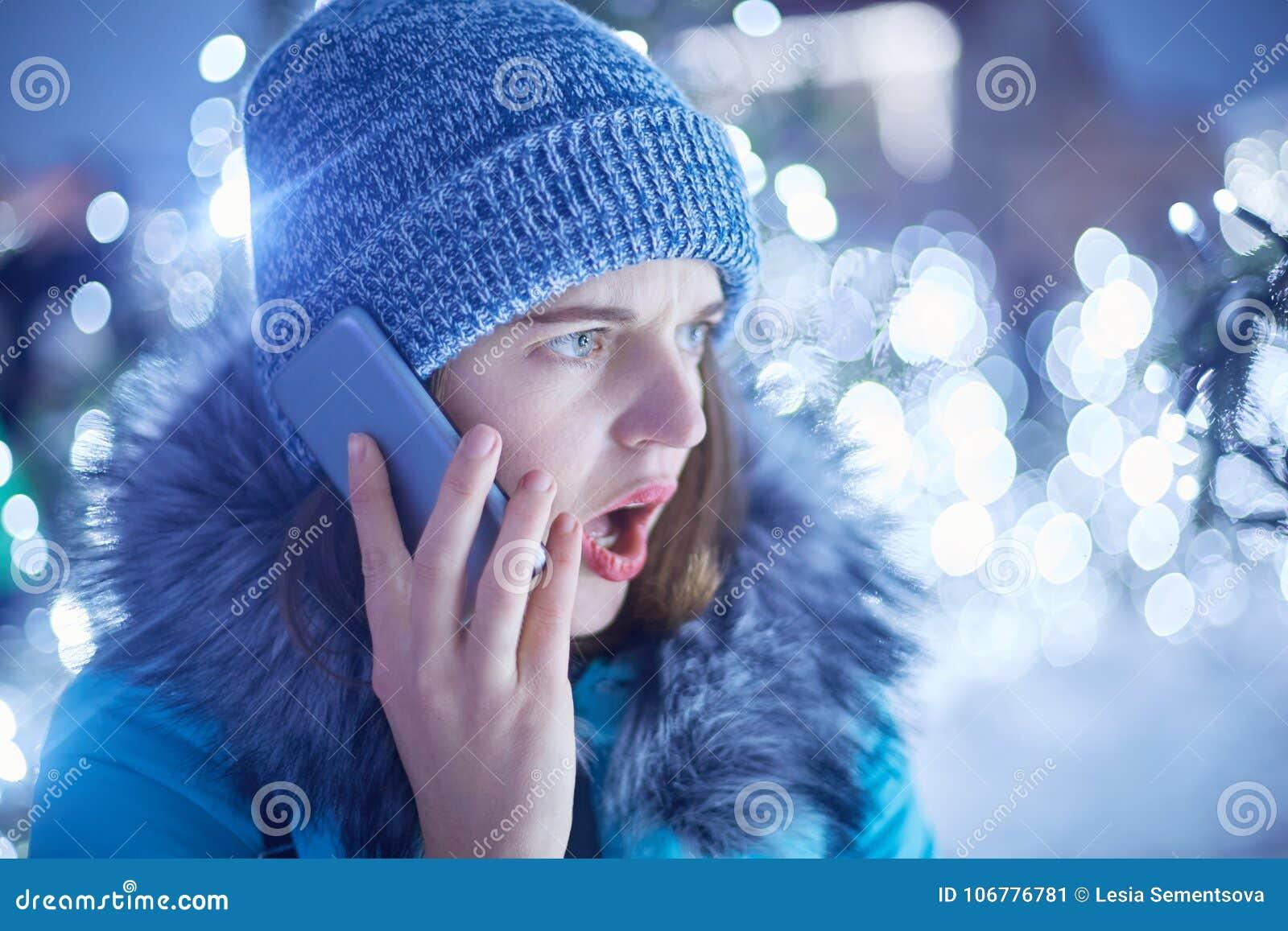 Η έκπληκτη γυναίκα που ντύνεται στα χειμερινά ενδύματα, ανοίγει το στόμα στο bewilderrment, μιλά με το φίλο της μέσω του έξυπνου