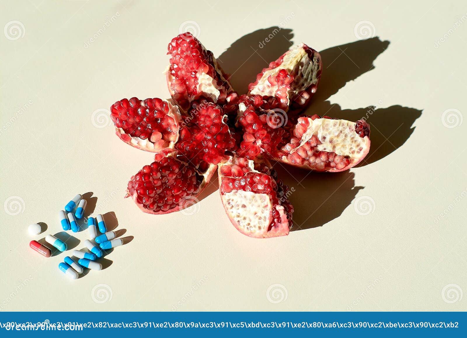 Η έννοια μιας υγιούς ζωής Ώριμα κόκκινα juicy ρόδι και χάπια, κάψες, χάπια που βρίσκονται χωριστά σε ένα άσπρο υπόβαθρο