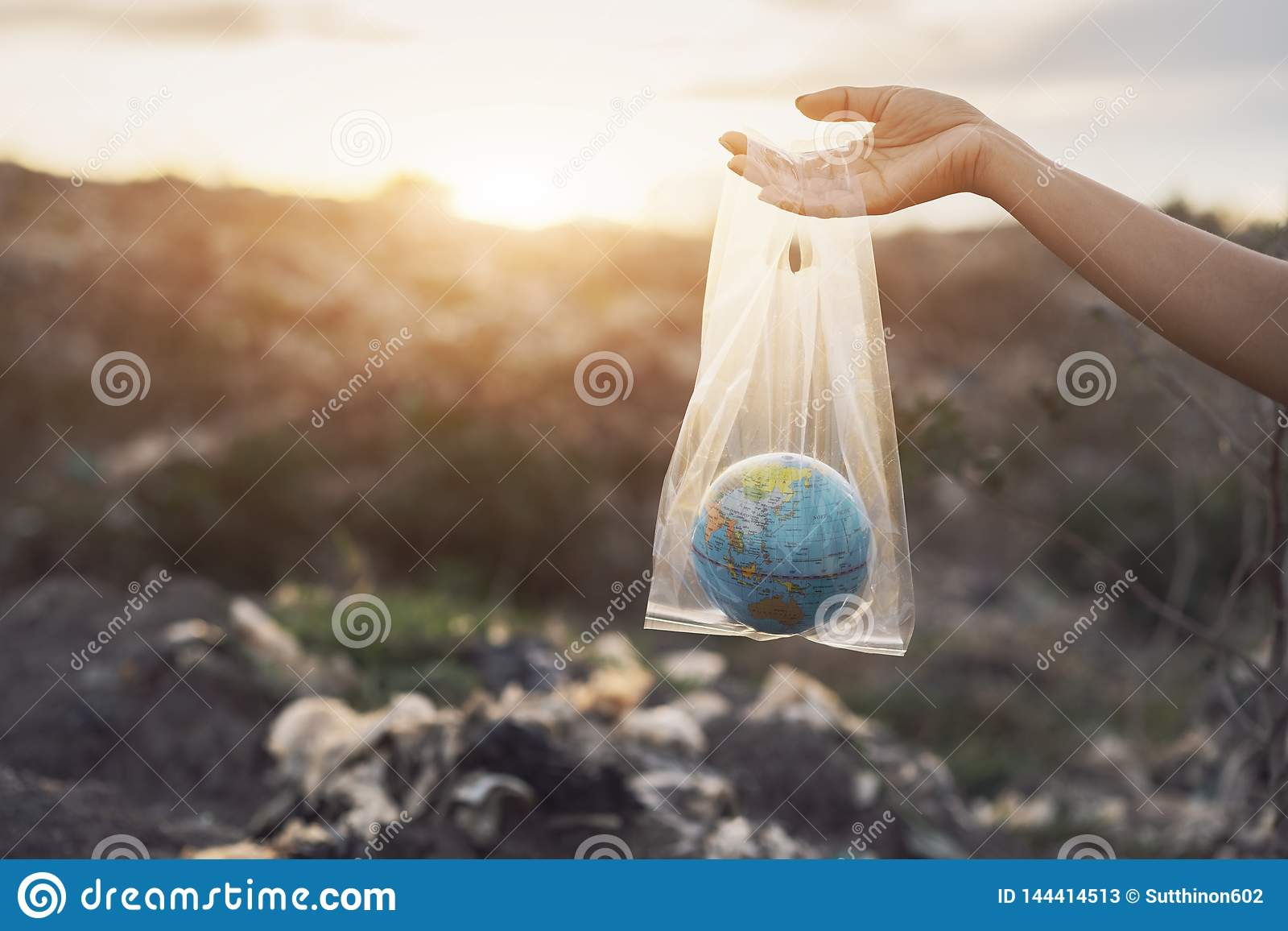 Η έννοια της ημέρας παγκόσμιου περιβάλλοντος Το χέρι γυναικών κρατά τη γη σε μια πλαστική τσάντα στο σωρό απορριμάτων στην απόρρι