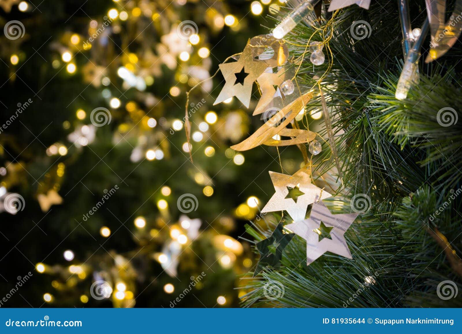 Η ένωση αστεριών στο χριστουγεννιάτικο δέντρο με το φως bokeh στο πράσινο κίτρινο χρυσό χρώμα, αφηρημένο υπόβαθρο διακοπών, θαμπά