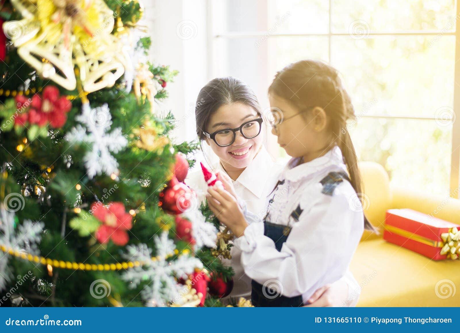 Η αδελφή κάνει ένα κιβώτιο δώρων Χριστουγέννων στη νεώτερη αδελφή για τις διακοπές Χριστουγέννων, ευτυχής και χαμογελώντας από κο