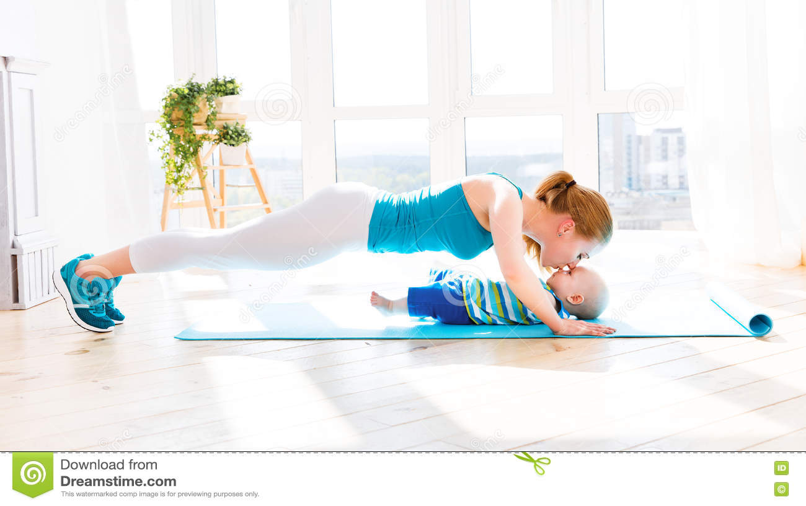Η αθλητική μητέρα συμμετέχει στην ικανότητα και τη γιόγκα με το μωρό στο σπίτι