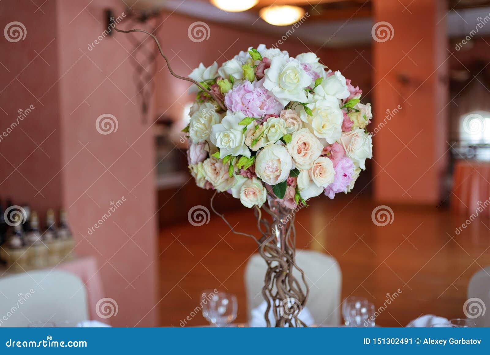 Η ανθοδέσμη των λουλουδιών σε ένα πόδι στο εσωτερικό του εστιατορίου για έναν εορτασμό ψωνίζει floristry ή σαλόνι γάμου