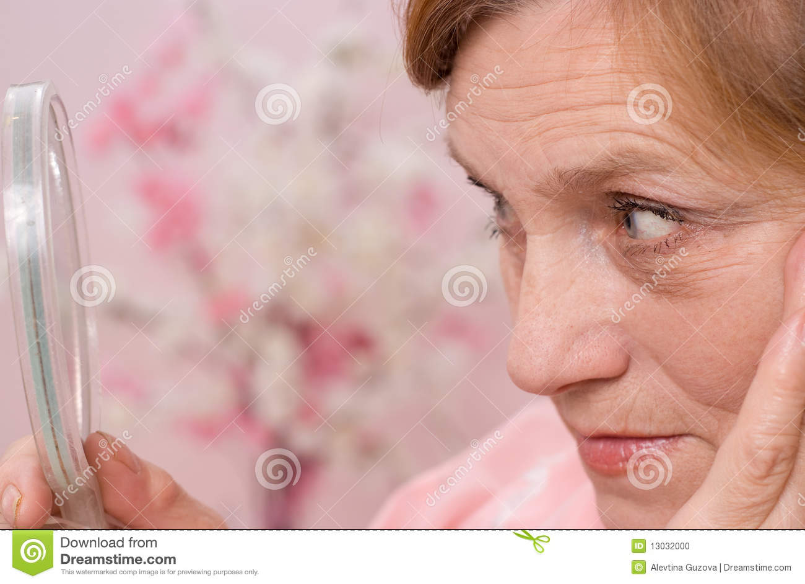 Η αρκετά ηλικιωμένη γυναίκα κοιτάζει στον καθρέφτη