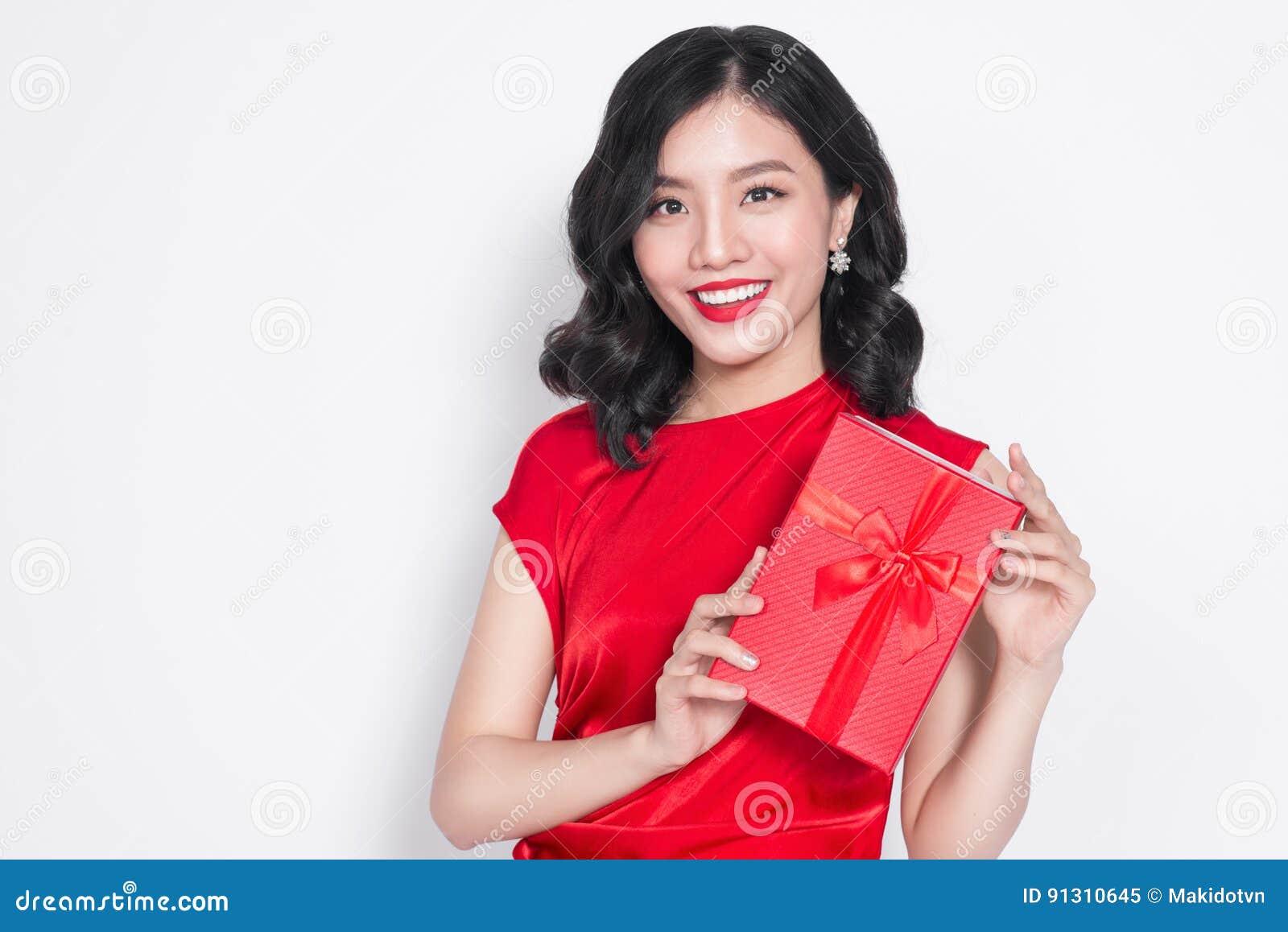 Η αρκετά νέα ασιατική γυναίκα έντυσε στο κόκκινο φόρεμα με ένα παρόν