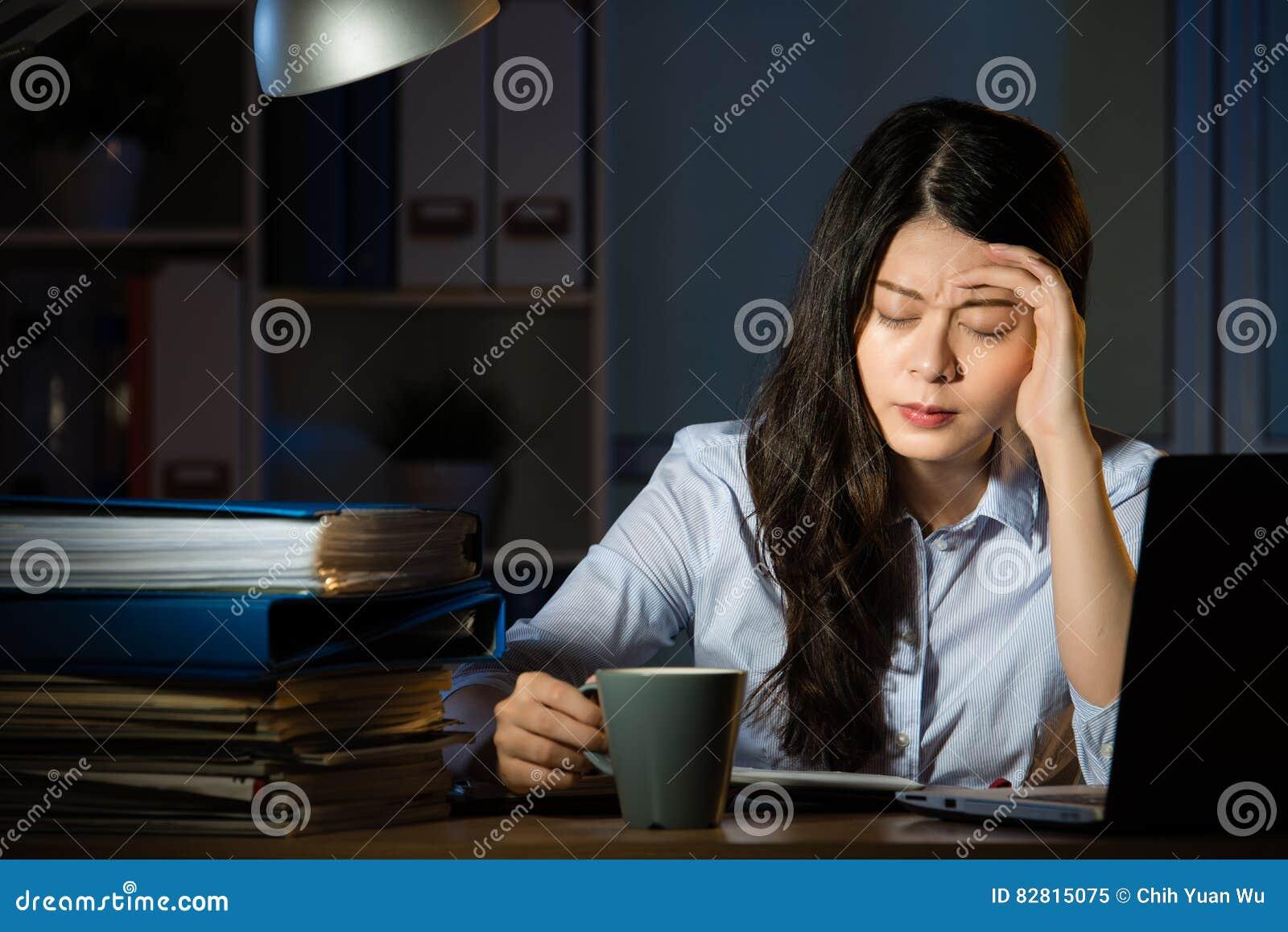 Η ασιατική επιχειρησιακή γυναίκα πίνει τις υπερωρίες πονοκέφαλου καφέ εργαζόμενος αργά