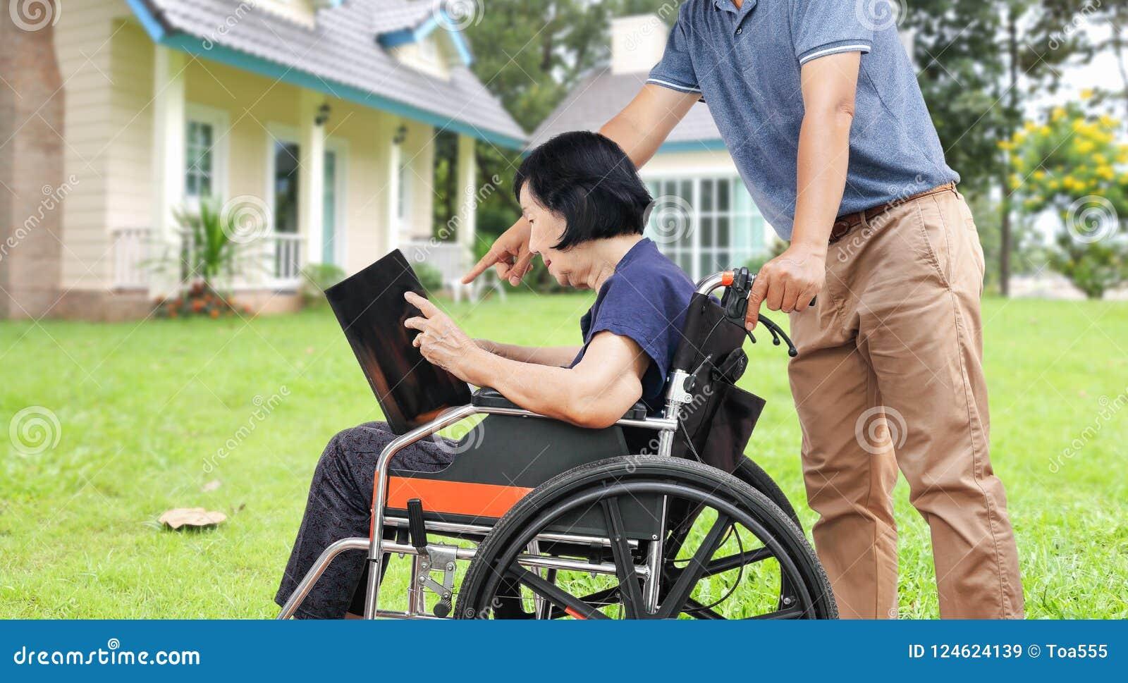 Η ασιατική ηλικιωμένη γυναίκα που διαβάζει ένα βιβλίο με το γιο της παίρνει την προσοχή στην ΤΣΕ