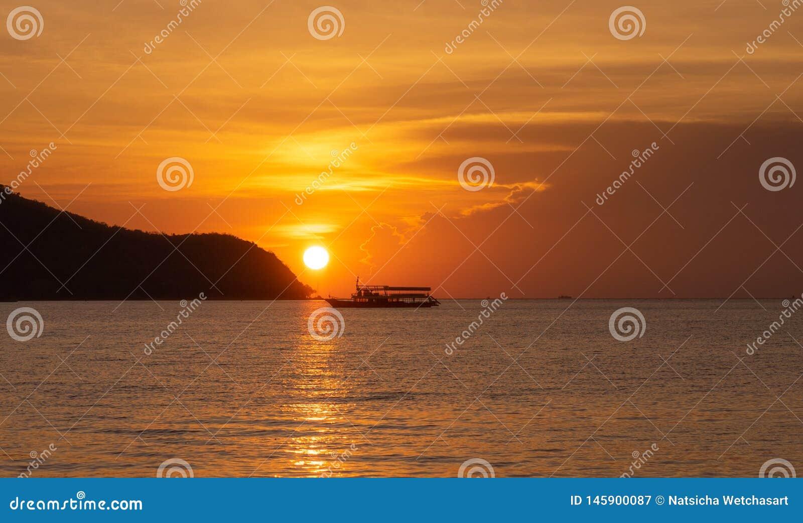 Η βάρκα ψαράδων σκιαγραφιών που επιπλέει στη θάλασσα κατά τη διάρκεια του χρυσού ηλιοβασιλέματος με τον ήλιο απεικονίζει στο νερό