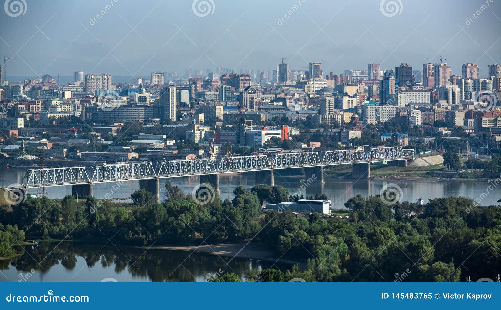 Η γέφυρα σιδηροδρόμων πέρα από τον ποταμό ενάντια στο σκηνικό μιας σύγχρονης πόλης