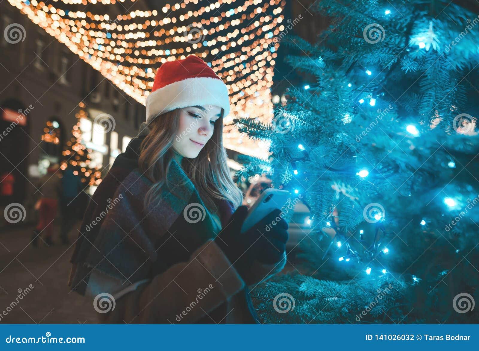 Η γλυκιά γυναίκα σε ένα καπέλο Χριστουγέννων στέκεται σε ένα δέντρο σε μια οδό που διακοσμείται σε διακοπές και χρησιμοποιεί ένα