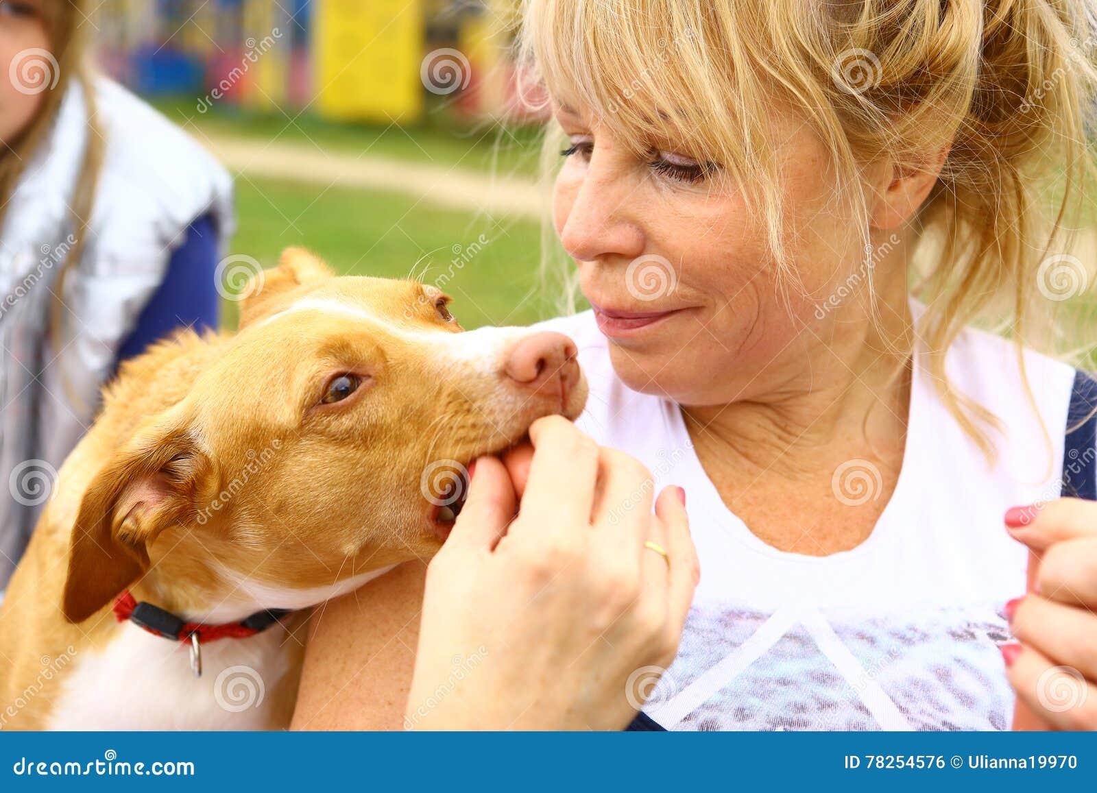 Η γυναίκα δίνει το λουκάνικο στο σκυλί