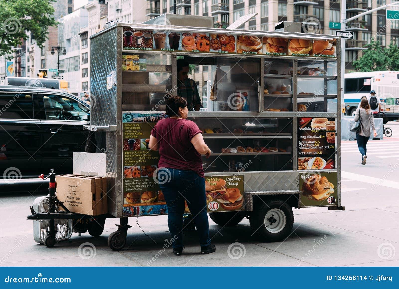 Η γυναίκα αγοράζει τα τρόφιμα στο φορτηγό τροφίμων στη Νέα Υόρκη