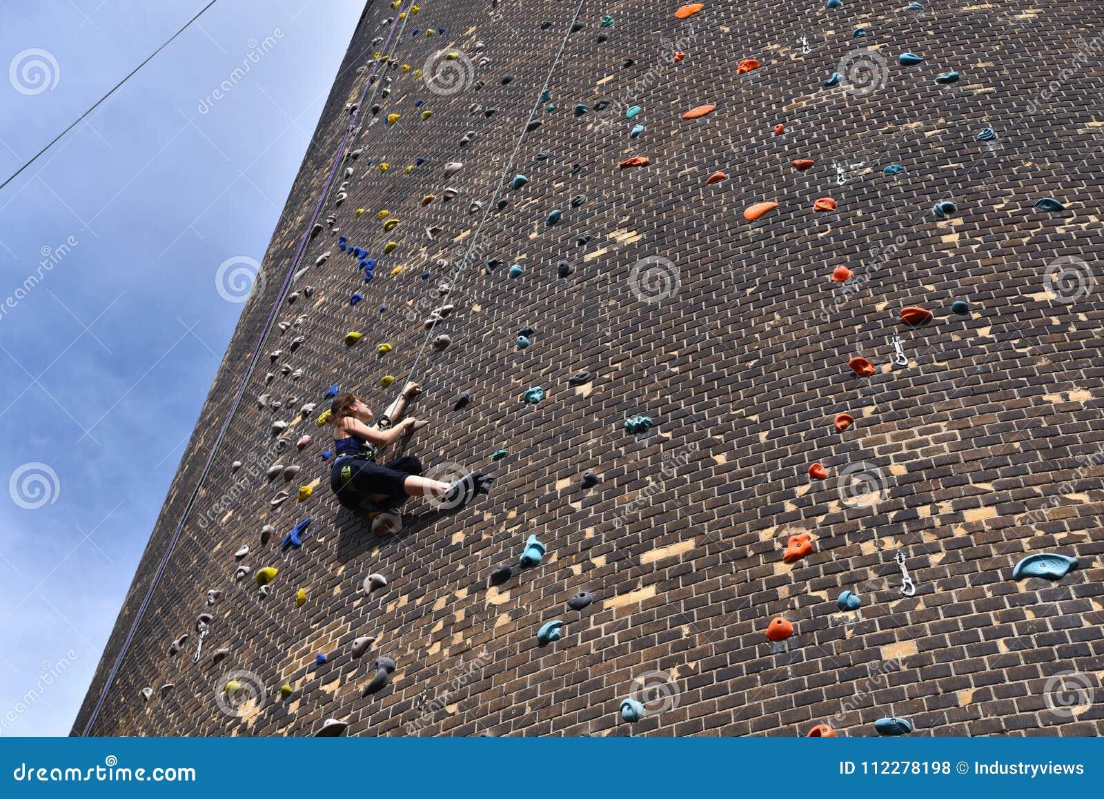 Η γυναίκα αναρριχείται επάνω σε έναν τεχνητό τοίχο βράχου - που εξασφαλίζεται με έναν άργυρο σχοινιών