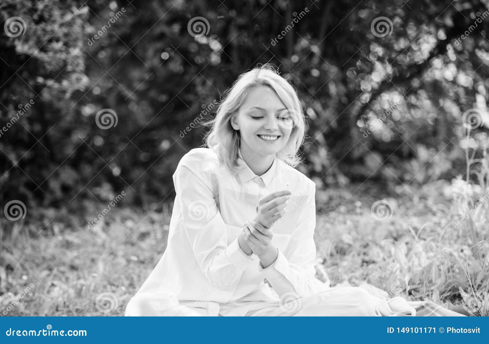 Η γυναίκα απολαμβάνει χαλαρώνει το υπόβαθρο φύσης Η κυρία απολαμβάνει το τρυφερό άρωμα λουλουδιών Θηλυκότητα και τρυφερότητα Τρυφ