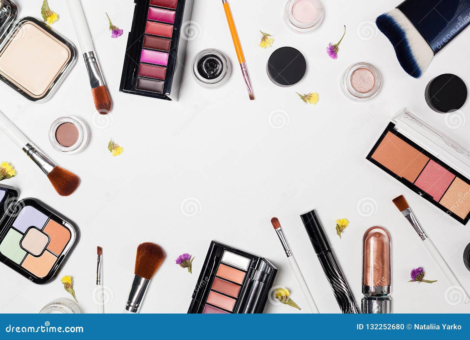 Η γυναίκα αποτελεί τα προϊόντα και τα εξαρτήματα στο άσπρο υπόβαθρο επαγγελματικά διακοσμητικά καλλυντικά, makeup εργαλεία