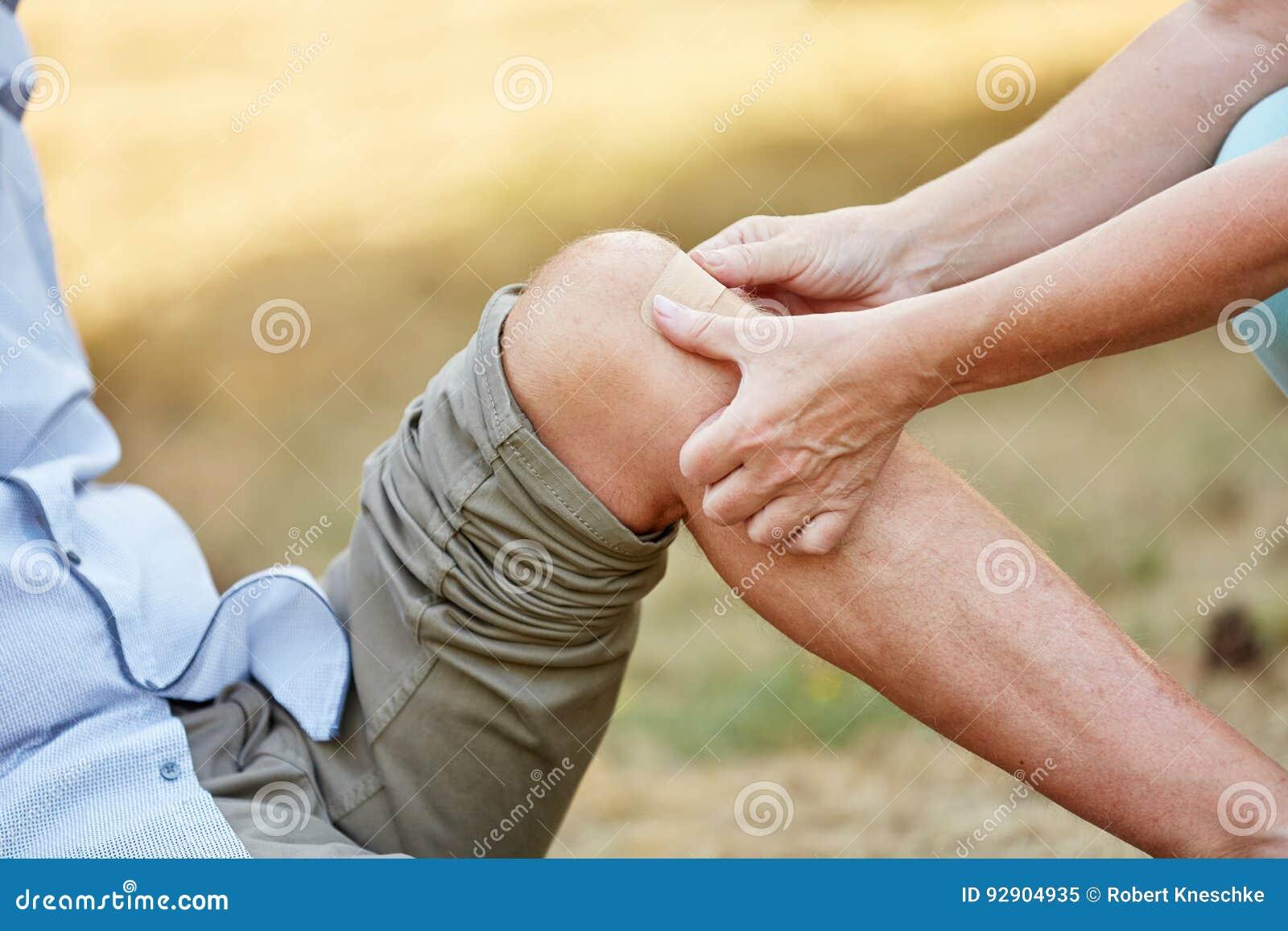 Η γυναίκα βάζει μια ενίσχυση ζωνών σε ένα τραυματισμένο γόνατο