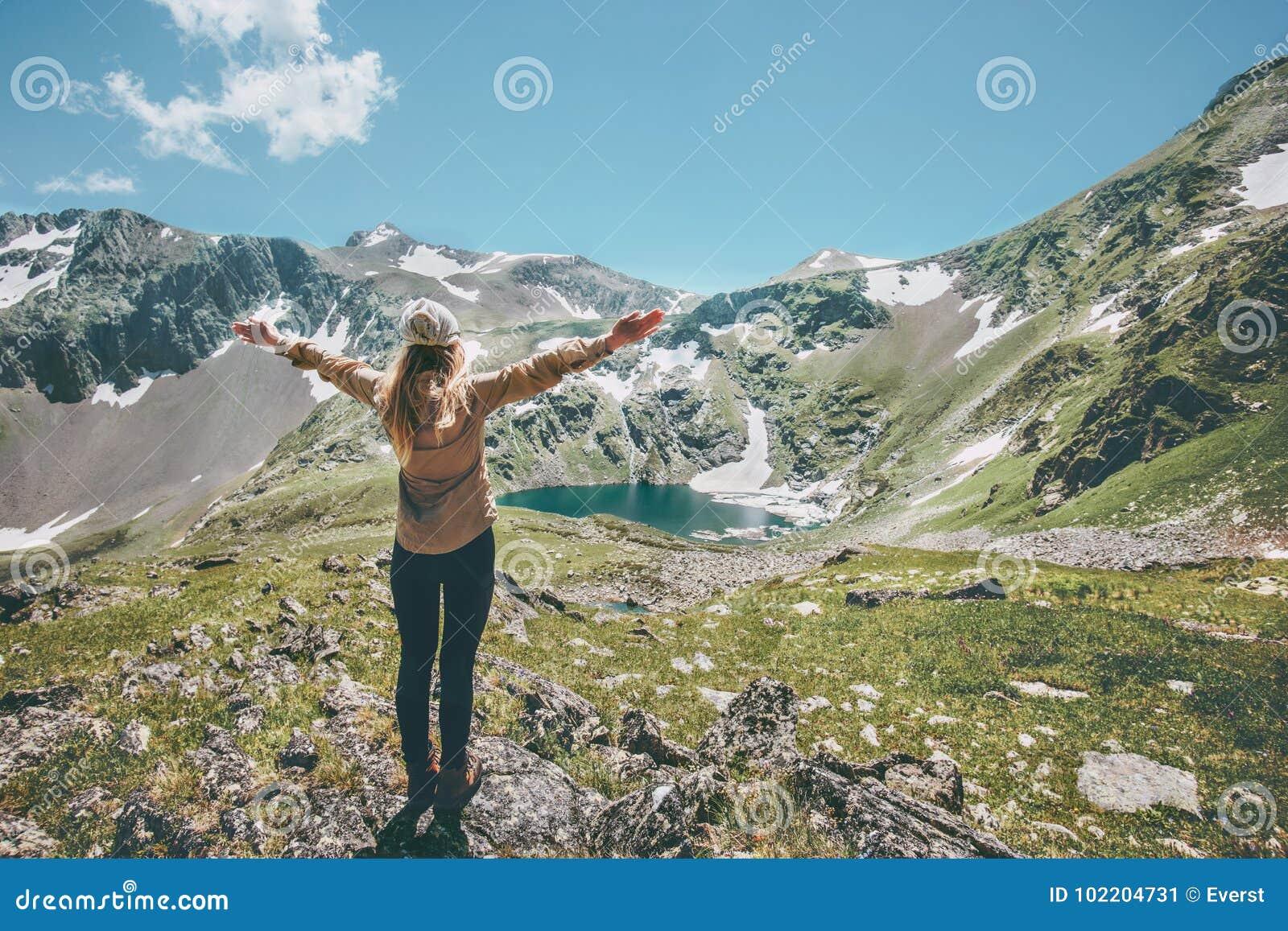 Η γυναίκα δίνει αυξημένος απολαμβάνοντας την περιπέτεια τρόπου ζωής ταξιδιού βουνών και λιμνών τοπίων