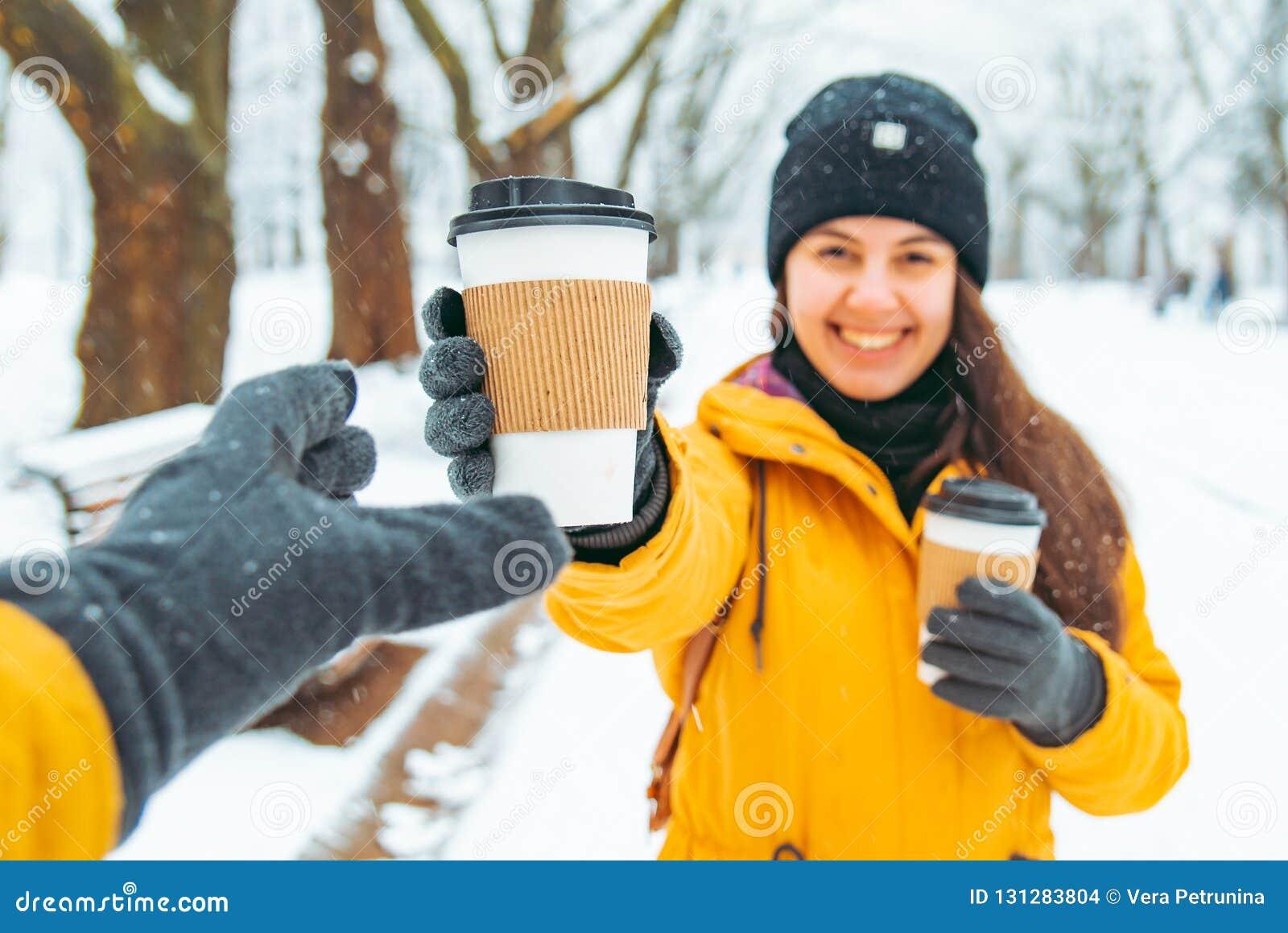 Η γυναίκα δίνει το φλιτζάνι του καφέ στο φίλο συνεδρίαση στο χιονισμένο χειμερινό πάρκο