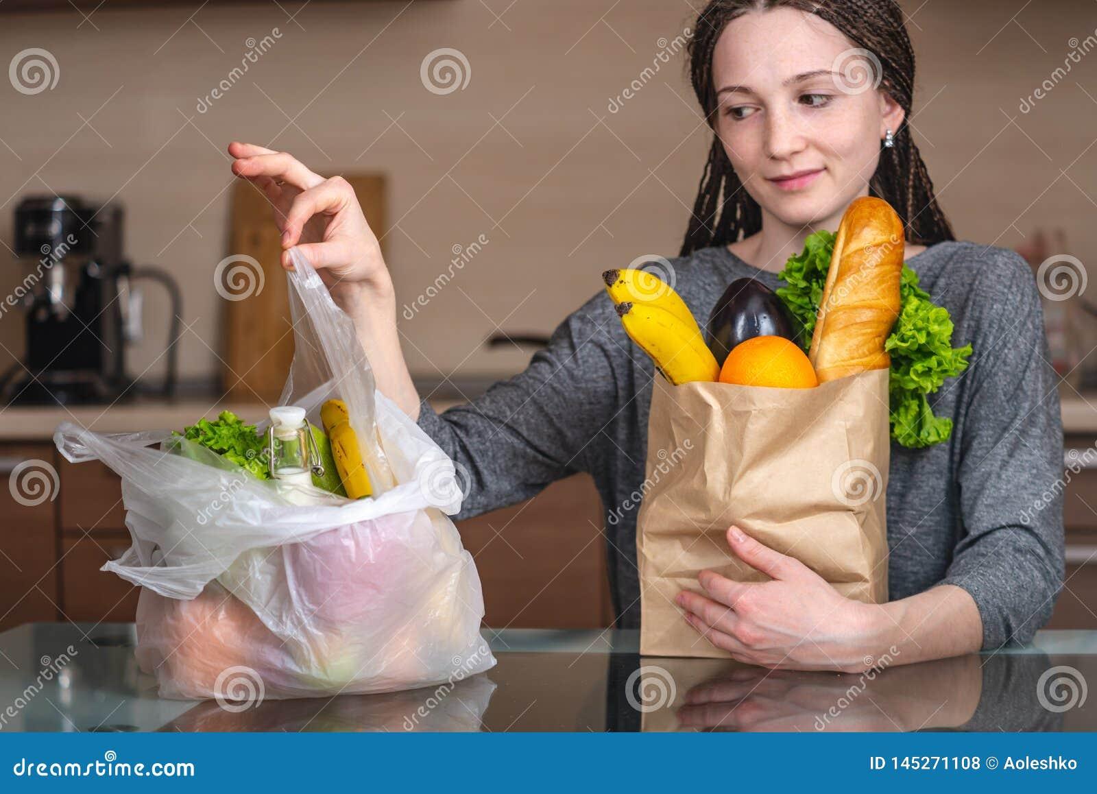 Η γυναίκα επιλέγει μια τσάντα εγγράφου με τα τρόφιμα και αρνείται να χ
