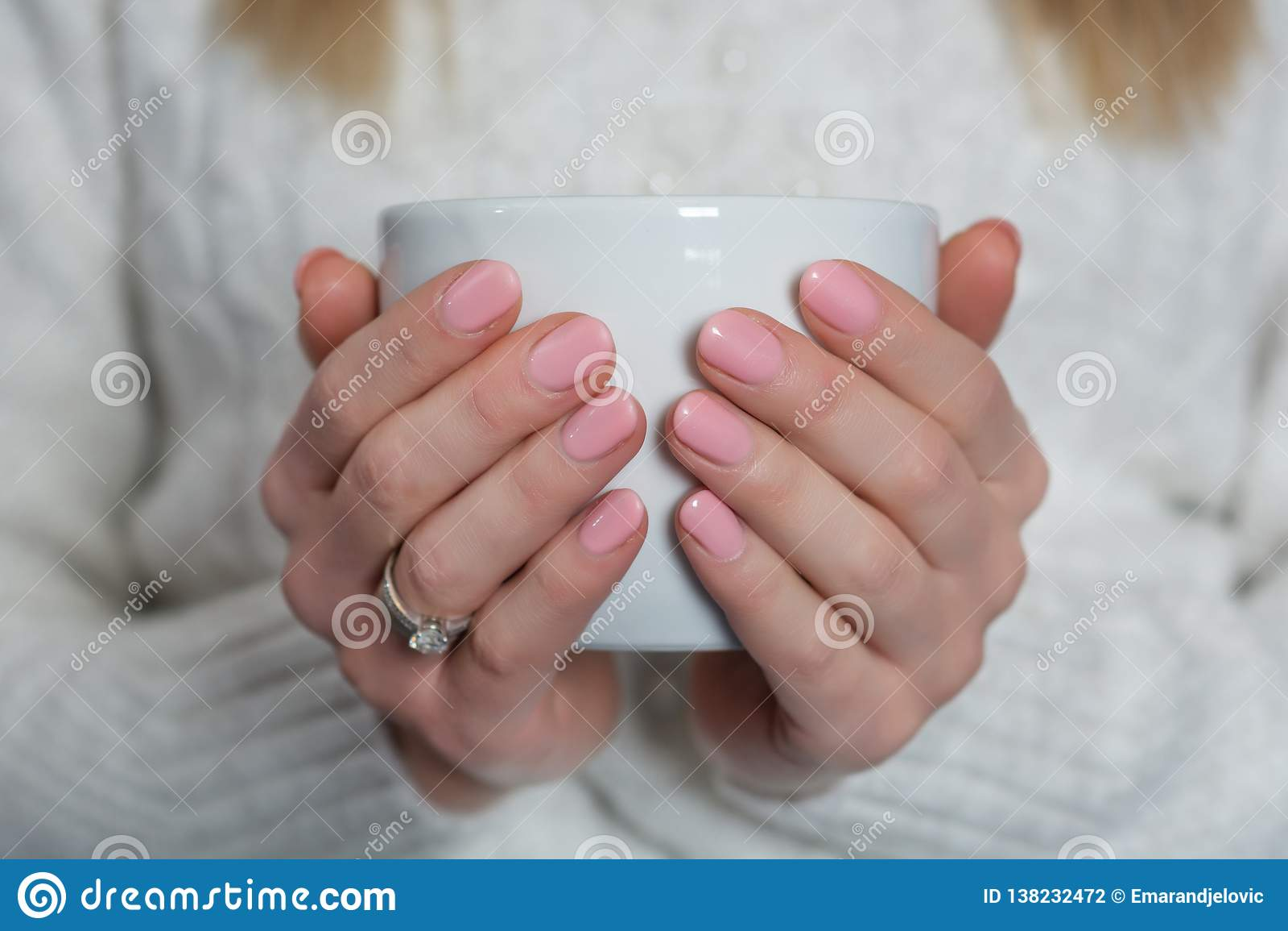 Η γυναίκα με τα ρόδινα καρφιά χρώματος μωρών γυαλίζει το πήκτωμα στα δάχτυλα κρατώντας το φλυτζάνι του τσαγιού