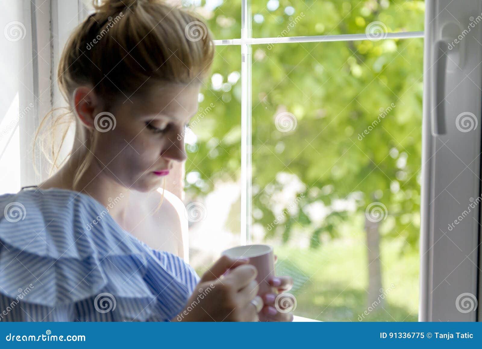 Η γυναίκα πίνει τον καφέ