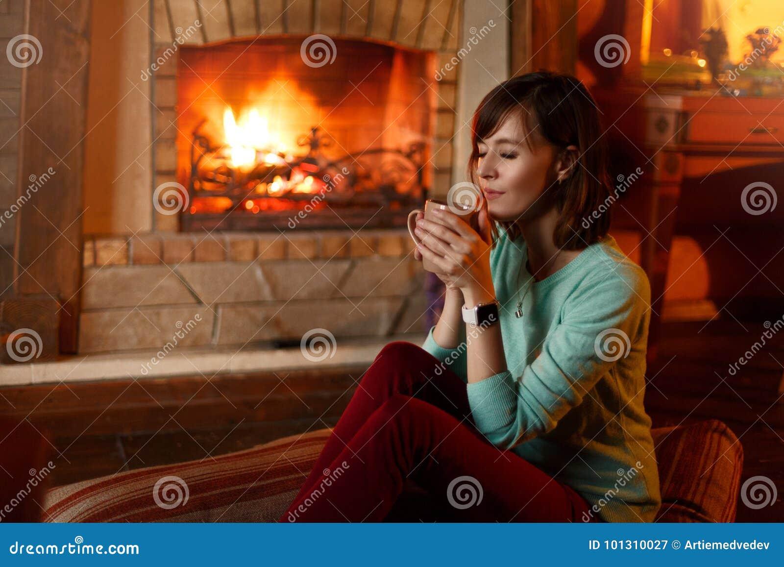 Η γυναίκα πίνει το τσάι και θερμαίνεται από την εστία Το νέο καυκάσιο θηλυκό κρατά το φλιτζάνι του καφέ στο σπίτι θερμός