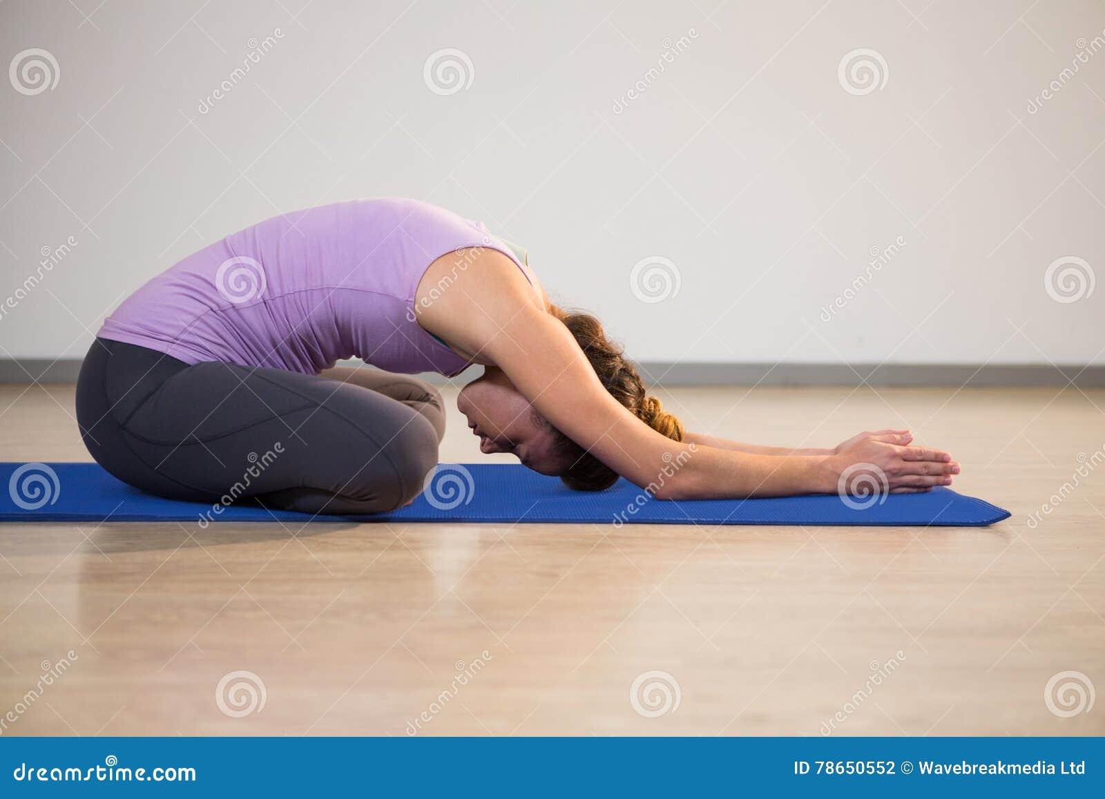 Η γυναίκα που κάνει το παιδί γιόγκας θέτει στο χαλί άσκησης