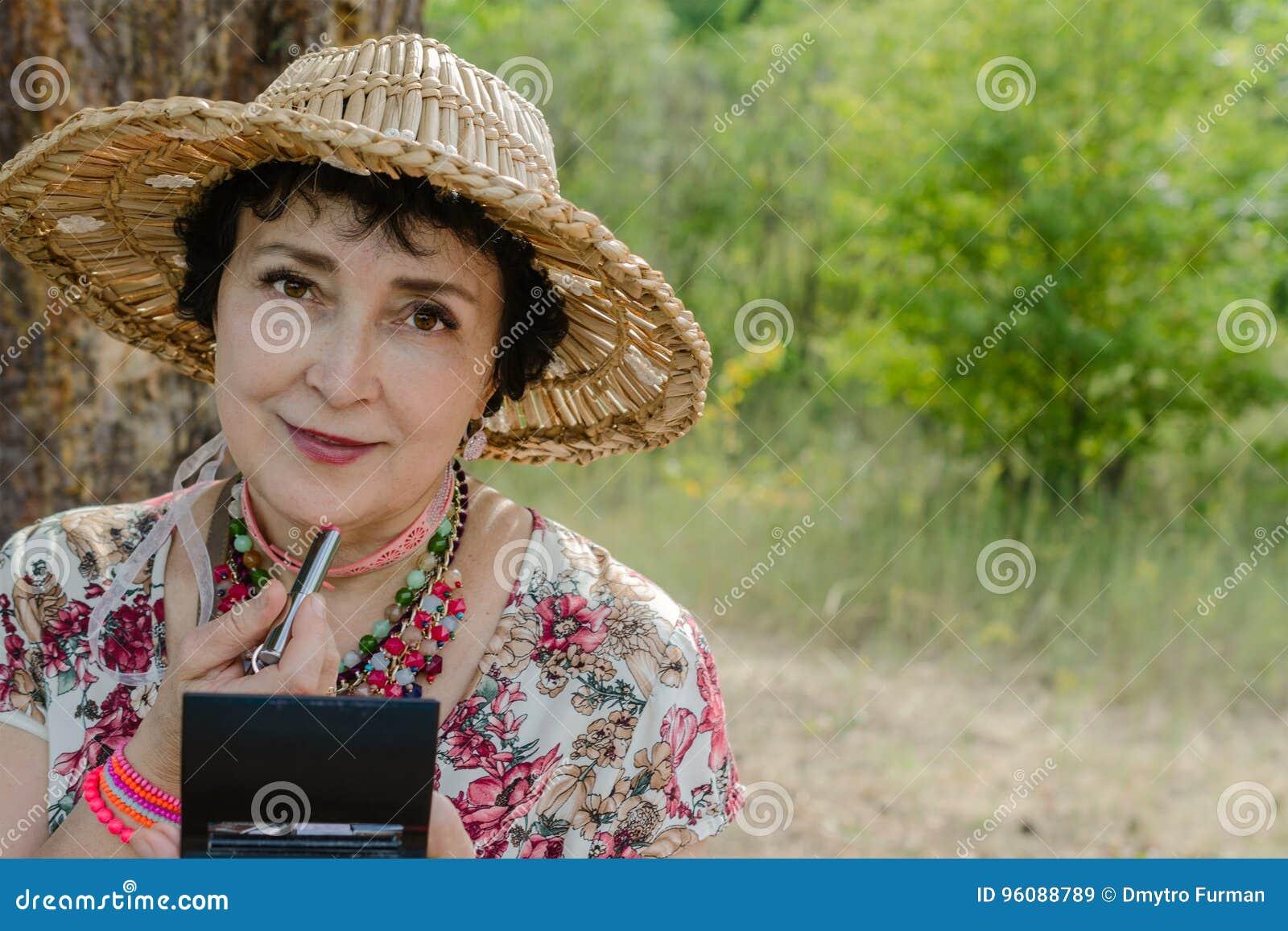 Η γυναίκα που φορά ένα καπέλο αχύρου, χρησιμοποιεί το κραγιόν της στη φύση