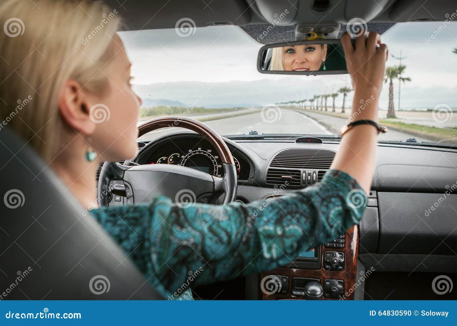 Η γυναίκα στο αυτοκίνητο κοιτάζει στον οπισθοσκόπο καθρέφτη