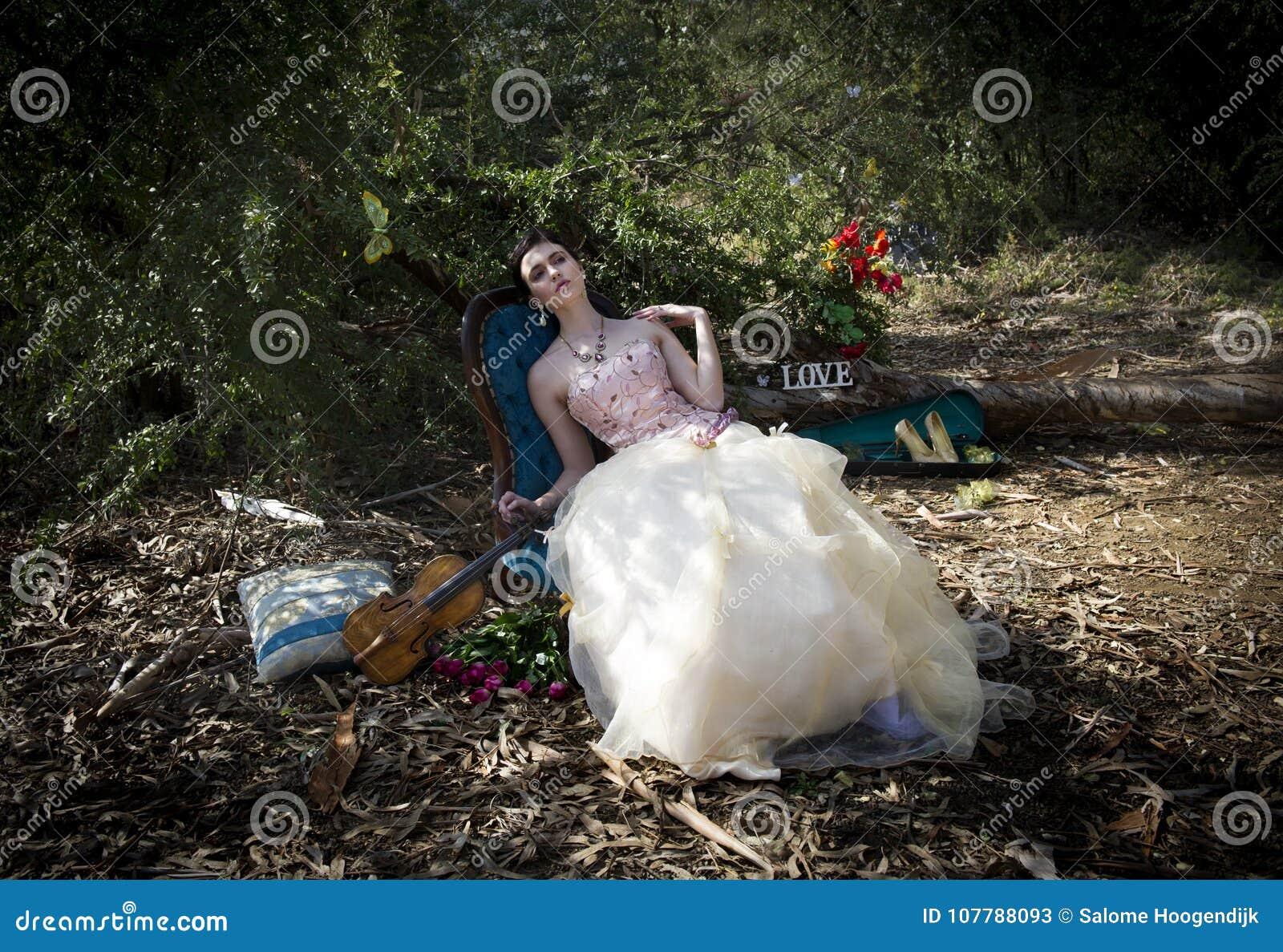 972fbb642d0 Η γυναίκα στο εκλεκτής ποιότητας ξάπλωμα φορεμάτων ραπτικών στη στυλ ροκοκό  καρέκλα στη μέση το δάσος