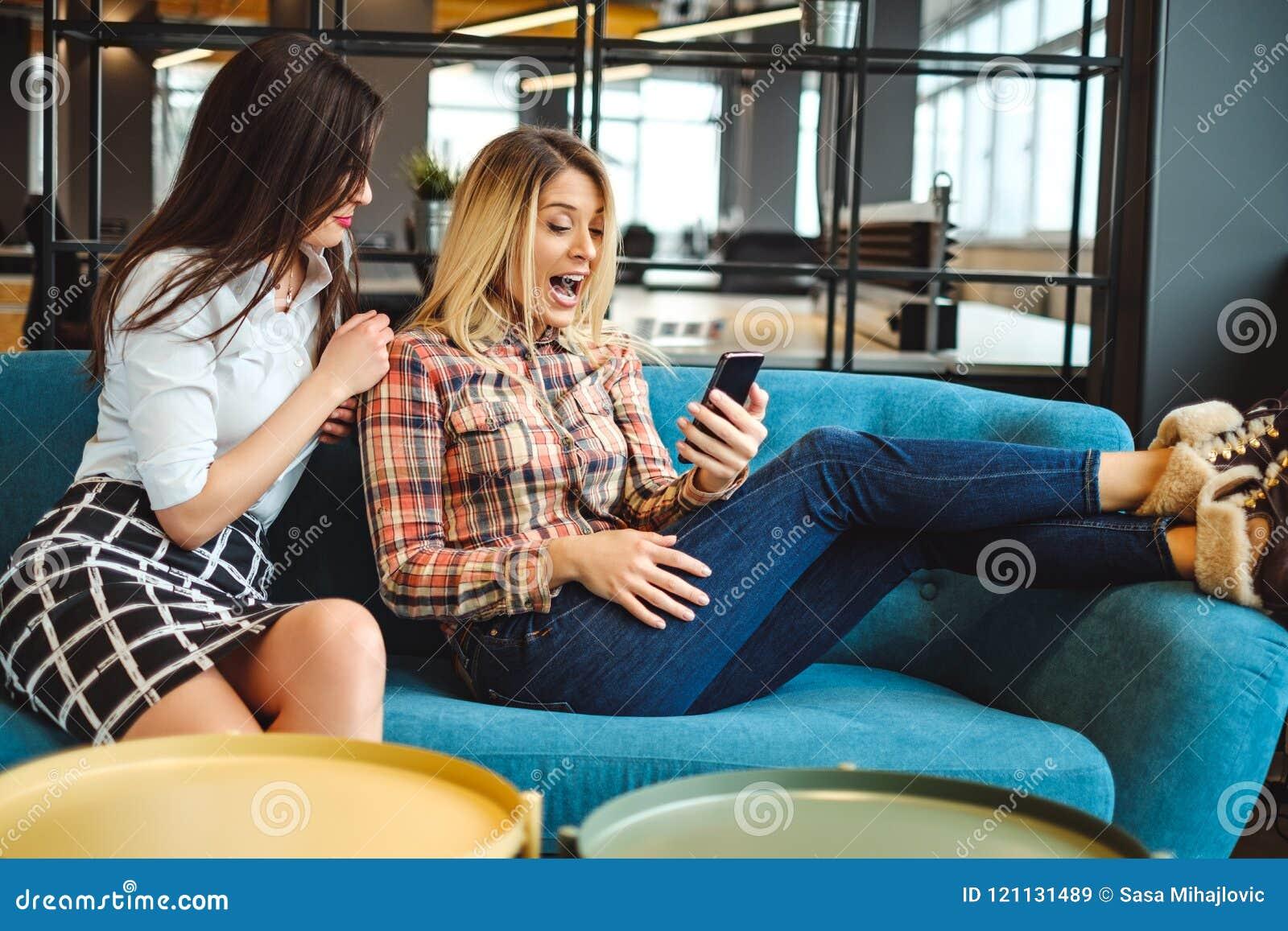 Η γυναίκα συνάδελφοι στο σπάσιμο εξέπληξε εξετάζοντας το κινητό pho